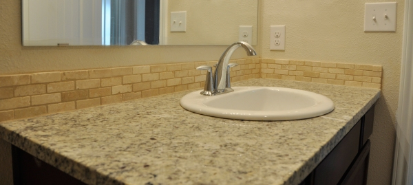 Granite countertops and travertive backsplash in the bathroom