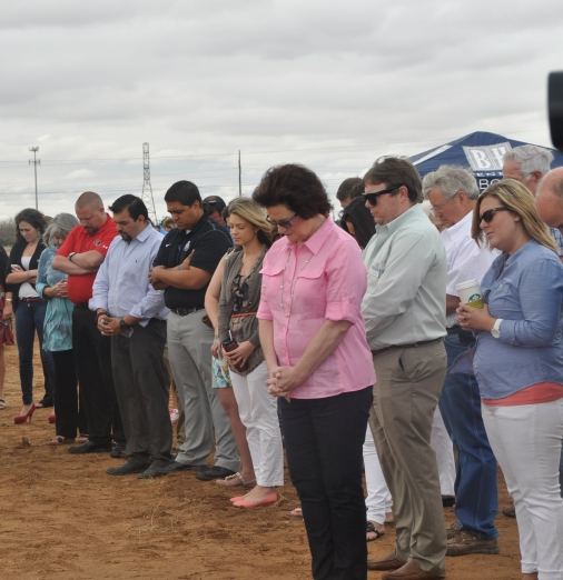 Attendees participate in prayer over new office building.