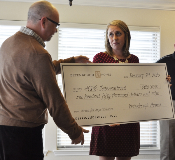 Rick Betenbough presents Leah Rutt, HOPE International representative, with a donation check.