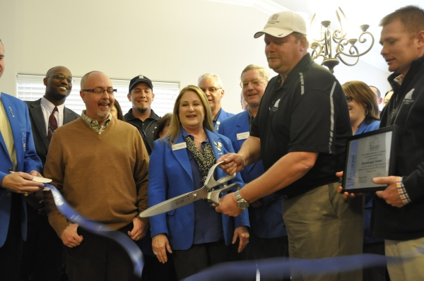 The M-Squad and Betenbough Homes employees participate in the ribbon cutting.